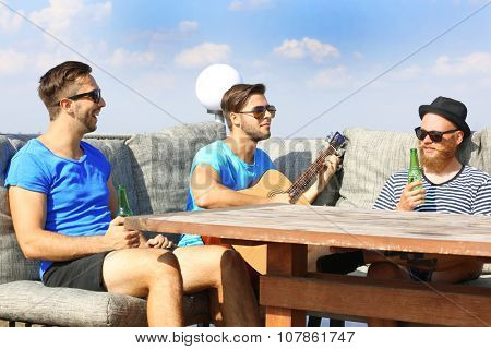 Yong men relaxing in cafe on the riverside and playing guitar