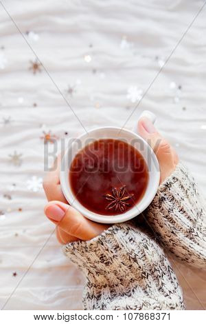 Woman Holds A Cup Of Hot Tea With Anise Star. Winter Fabric Background With Silver Snowflakes.