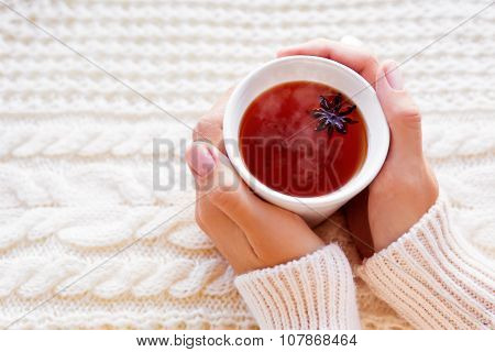 Women Holds A Cup Of Hot Tea With Anise Star. Beautiful Fabric Background With Knitted Pattern.