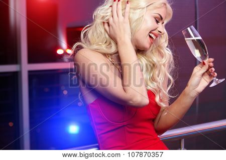 party, drinks, christmas, New Year concept - smiling woman in red dress with a glass of champagne