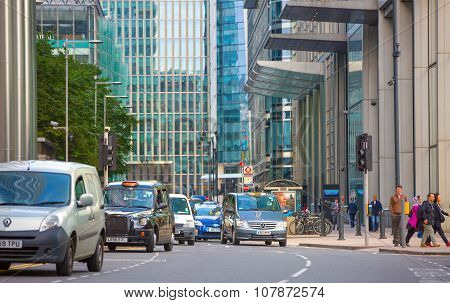 LONDON, UK - SEPTEMBER 9, 2015: Street of Canary Wharf with lots of business people and cars
