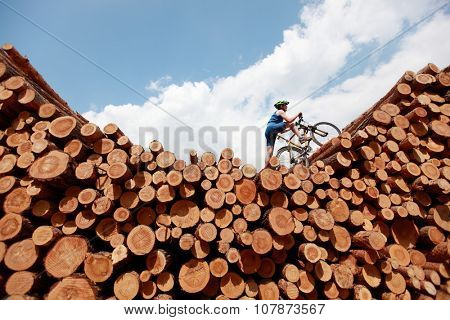 extreme cycling - fit man with his bicycle on top of large pile of logs