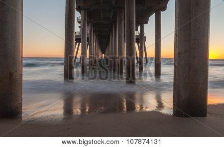 Under the Huntington Beach, California pier at sunset