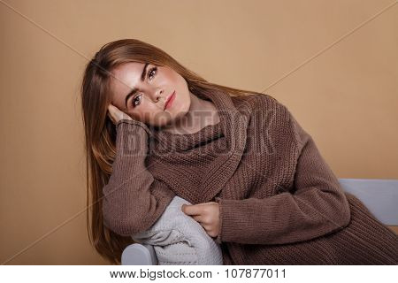 Girl In A Warm Sweater Leaning On The Arm Of The Sofa.