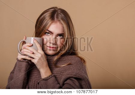 Girl In Warm Sweater Drinking A Warm Beverage From A Mug.