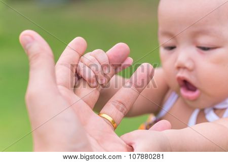 Child Holding Father's Hand At Public Park Outdoor
