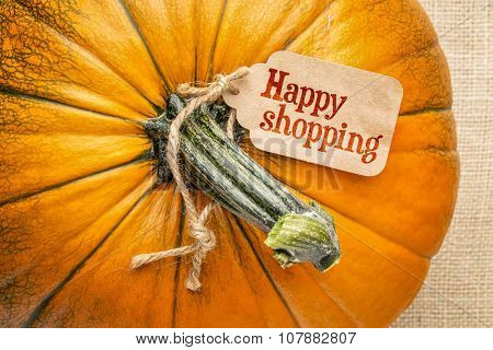 A pumpkin against burlap canvas with a happy shopping  price tag