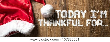 Today Im Thankful For... written on wooden background with Santa Hat