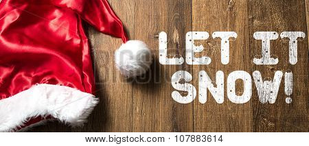 Let It Snow written on wooden background with Santa Hat