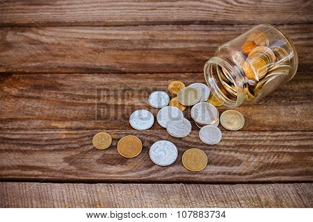 Coins spilling from glass jar on the old wooden background. Toned image