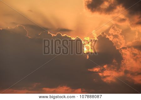View Of Rising Sunbeams From Behind Golden Cumulus Clouds