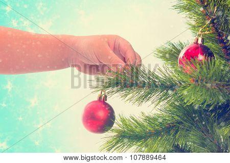 Child decorates Christmas tree.