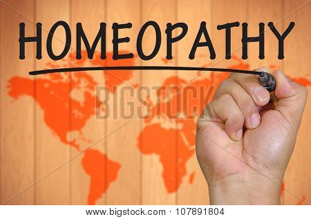 Hand Writing Homeopathy Over Blur World Background