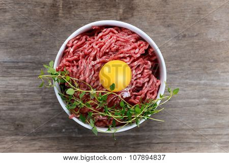 Fresh Raw Minced Beef With Egg On Wooden Table.