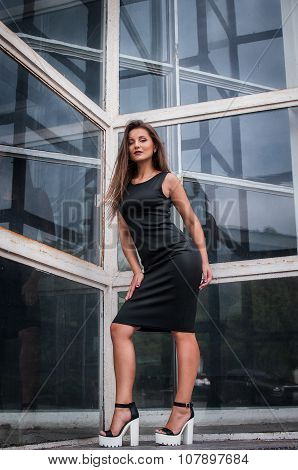 young girl standing indoor reflected in mirror on the wall looking away and thinking in black dress,