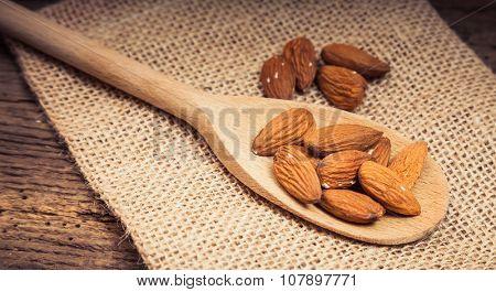 Fine almonds on wooden spoon