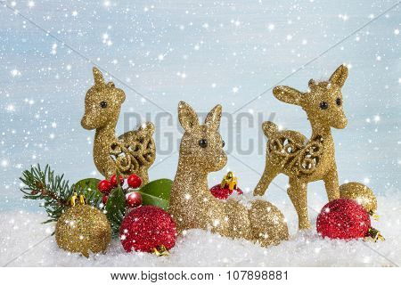 The family of deer with branch fir and holly leaves in the snow. Christmas background.