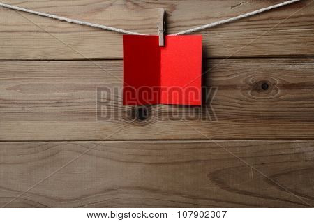 Red Greetings Card Pegged To String On Wood Plank Background