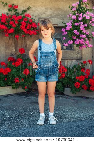 Summer portrait of a little girl of 6 years old, wearing denim overalls and grey shoes