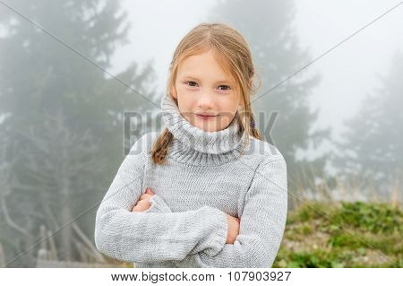 Cute little girl of 8 years old playing outdoors on a very foggy day, wearing grey warm pullover