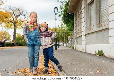 Autumn portrait of 2 adorable kids in a city, wearing warm pullovers and denim jeans