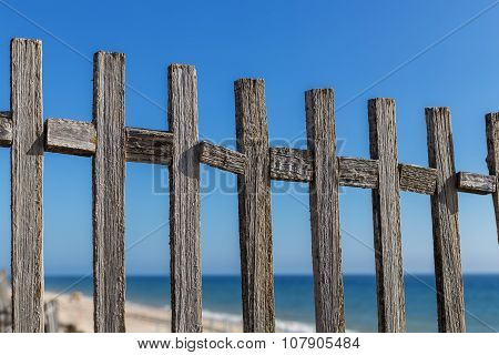 Antique Wooden Fence On The Background Of The Sea. Blue Sky.