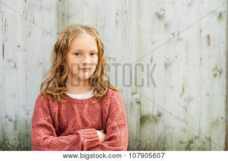Close up portrait of a cute little girl of 8 years old with curly hair