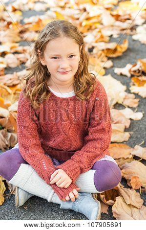 Autumn portrait of a cute little girl with curly hair, wearing terracota pullover, leg warmers and b