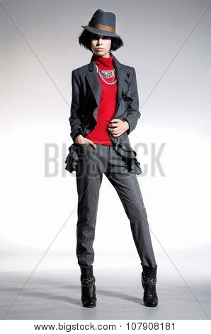 Full body fashion model in black coat clothes with hat  posing in studio