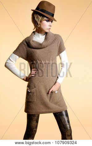fashion model in modern clothes with hat posing in studio