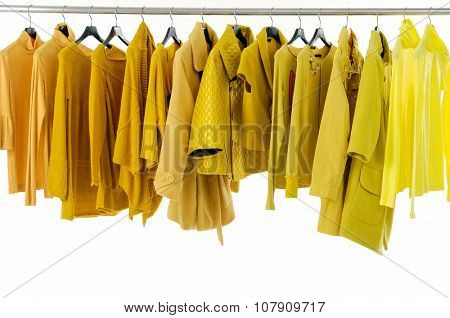 Variety of female yellow clothing on hangers