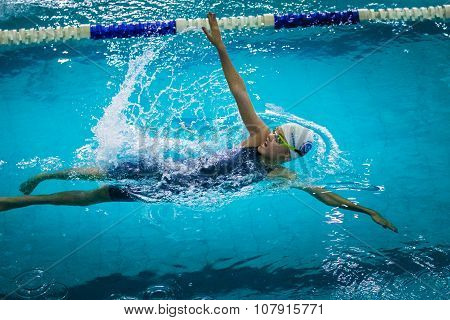 young beautiful girl swims backstroke