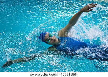 girl athlete swims backstroke, around her spray of water
