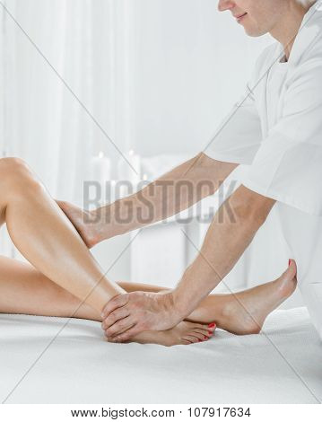 Physical Therapist Massaging Female Calf
