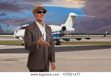 Elegant man welcoming at the airport next to a private jet