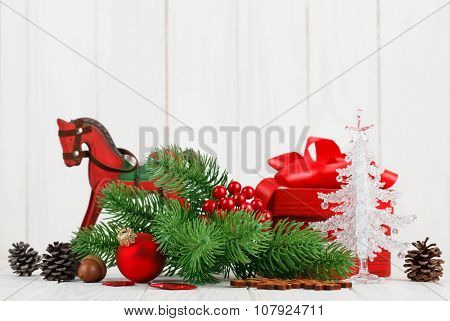 Christmas balls with branch fir and pinecone on wooden board.