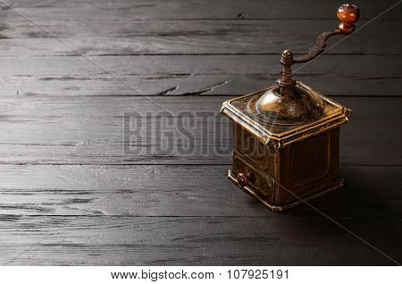 Old vintage bronze coffee grinder on black wooden board