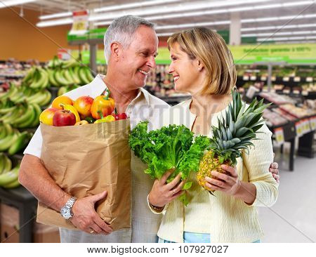 Senior couple with grocery bag of vegetables over market background.