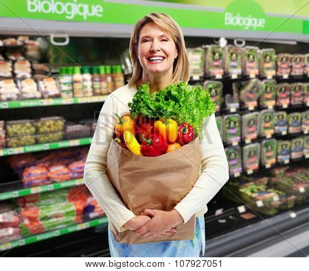 Woman with grocery bag of vegetables in a supermarket background.
