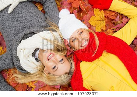 Two female friends laying in leafs
