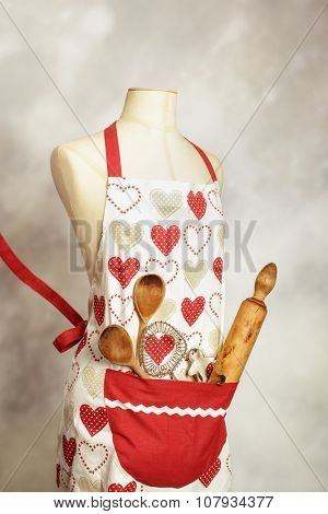 Colorful apron on mannequin with utensils in pocket