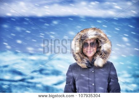 Portrait of cute happy woman on vacation, having fun outdoors enjoying snowfall, wearing stylish warm coat with fur on hood, winter fashion concept