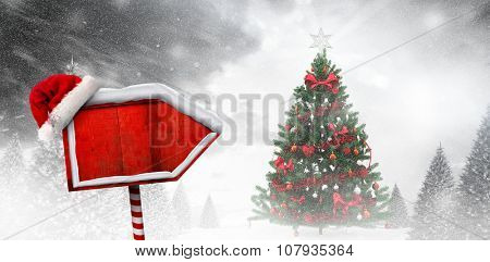 Santa sign against christmas tree in snowy forest