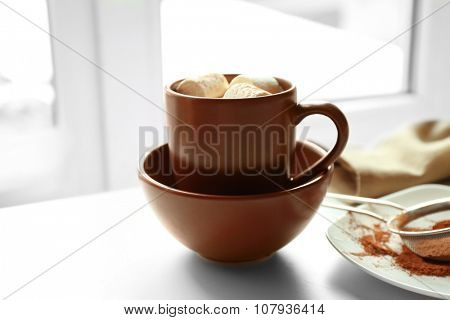 Cup of coffee with marsh mellow on a table in kitchen