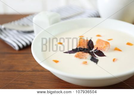 Delicious salmon cream soup in white plate on wooden table, close up