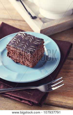 Sweet chocolate cake on blue plate with cup of tea on brown cotton serviette, close up