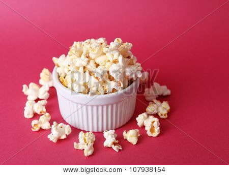 Salted popcorn on pink background