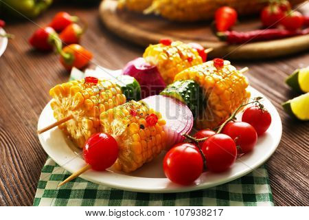 Delicious grilled corn served with vegetables and green plaid pattern napkin