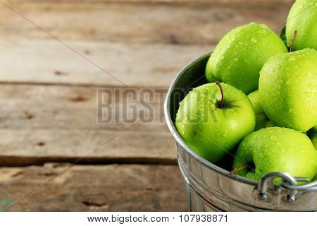 Ripe green apple in metal bucket on wooden table close up