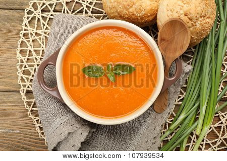 Carrot cream-soup with buns on table close up